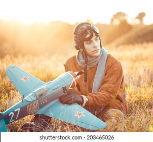 Young guy in vintage clothes pilot with an airplane model outdoors