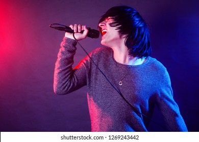 The young guy vocalist is screaming in microphone on stage on concert illuminated with red and blue lights.