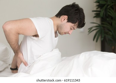 Young guy wearing white t-shirt sitting indoor on the bed feeling sudden ache in his back, suffering from backpain, need to make doctor appointment. Healthcare and treatment concept