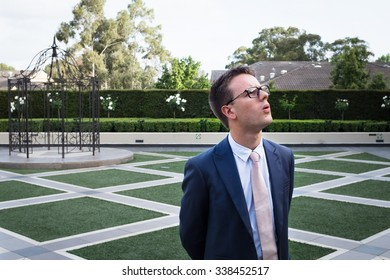 Young Guy at Wedding with Glasses and Blue Suit looking up to side and Frowning