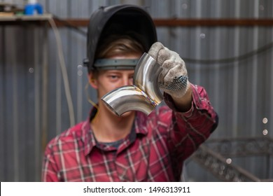 Young guy welder in a checkered red shirt show a stainless steel pipe argon welded iron workshop. Modern welding methods.