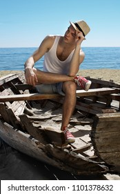 A young guy in a white T-shirt and hat is sitting in an old boat on the seaside. He holding his hat and looks to the side with confidence.