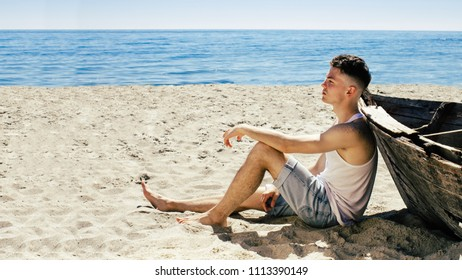 A young guy in white T-shirt relax on the beach. He is sitting near the old boat. He is holding hat on his hand and looking dreamly far away.