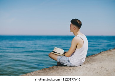 A young guy in a white T-shirt is sitting on the pier. He enjoys a beautiful view and thinks about future travels. What could be better than a holiday on the seaside.