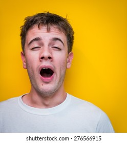 Young Guy in White T-Shirt Yawning. Yellow Background