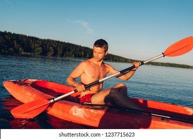young guy without a t-shirt is swimming on a red kayak with a paddle in his hands, close-up