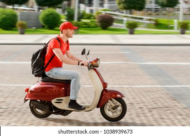Young guy working as deliveryman. Man is driving a bike down a paved road, delivering an order to the place.