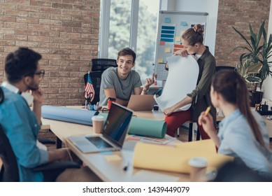 Young guys anf girls working in meeting room while lady showing whatman paper with smile. Colleagues looking at her with interest