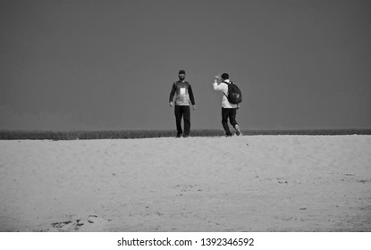 Young guys walking around a sandy coastal area unique photo