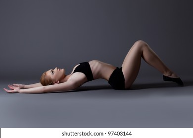 young gymnast girl in black top lay on background