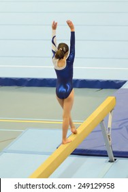 Young gymnast girl performing a choreographed routine on balance beam in an indoor competition.