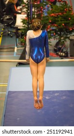 Young gymnast girl performing  a choreographed routine on high horizontal bar while practicing for the Christmas competition, Christmas tree in the background.