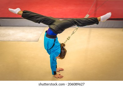 Young gymnast girl performing handstand with spread while practicing for the competition