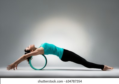 young gymnastics girl lying on pilates fitness ring wheel and relax body in gray wall background floor in yoga studio classroom.
