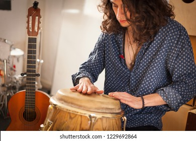 Young gypsy percussionist hands while playing congas instrument on a rehearsal studio with spanish guitar on the background. Membranophones percussion flamenco instruments concept. Musicology concept.