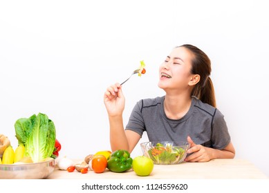 Young haapy Asian woman eating salad vegetable on white background