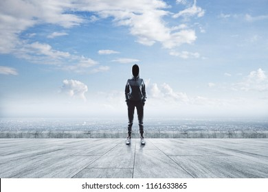 Young hacker standing on concrete rooftop with city and sky view. Malware and research concept