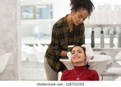 Young hair cutter with curly hair carefully drying up hair after washing. Brunette client in red sweater getting luxury treatment in beauty salon. Hairdresser cleaning girl's head before coiffure.