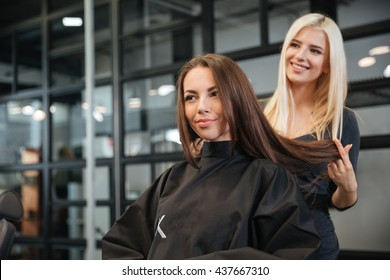 Young hairdresser giving a new haircut to female customer at parlor