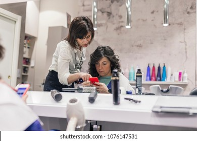 Young hairdresser talking with her client after a styling looking at the smartphone in beauty salon