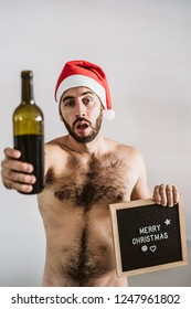 Young half drunk and handsome man with a naked torso wearing a Santa Claus hat celebrates Christmas time drinking wine. Small blackboard with text. Lifestyle.