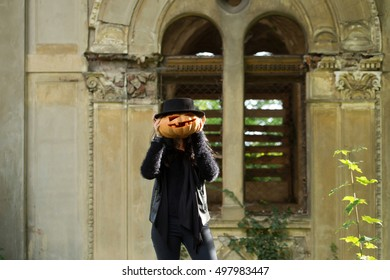 young halloween woman or girl in black witch hat near old ruined building with traditional autumn holiday symbol of orange spooky pumpkin outdoor on green natural background