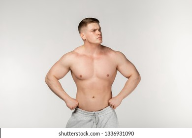 Young hamdsome bodybuilder posing in the studio over gray background, holds hands on waist, looking away. Sport lifestyle concept