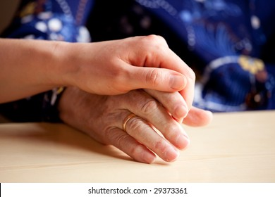 A young hand comforts and elderly hand