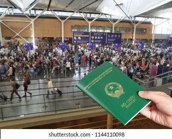 Young hand handing Vietnamese passport at airport custom counters, immigration concept