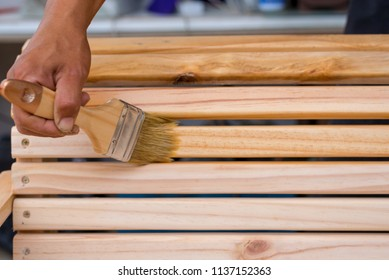 Young man's hand holding a brush applying varnish paint on a wooden furniture