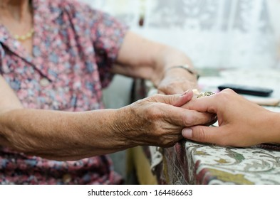 A young hand holding an old pair of hands