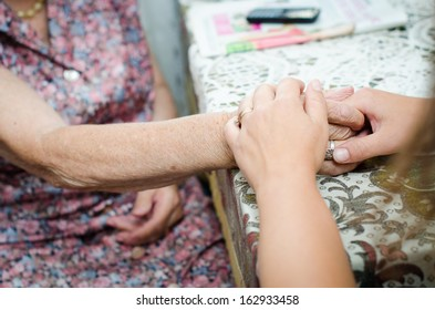 A young hand holding an senior pair of hands
