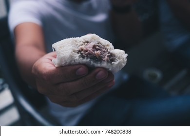 Young man's hand offering or showing filled meat bread called siopao, a Filipino version of the Chinese or Cantonese steamed bun called cha siu bao or baozi. Selective focus. Close up. Copy space.