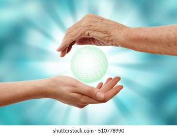 a young hand and an old one holding glowing globe