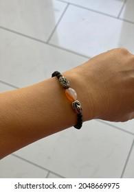 Une jeune femme à la main avec un bracelet avec des pierres noires