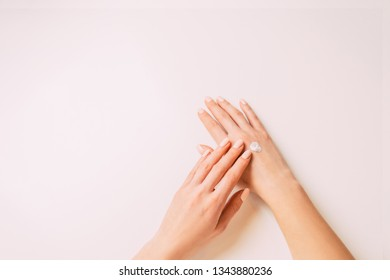 Young woman's hands applying moisturizing cream, point of view. Copy-space in left part of image.