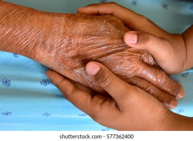 Young hands hold elderly hand on the bed hospital.