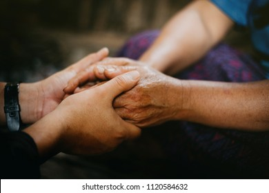 Young hands holding old hands and pray together,Pray for the elderly concept.