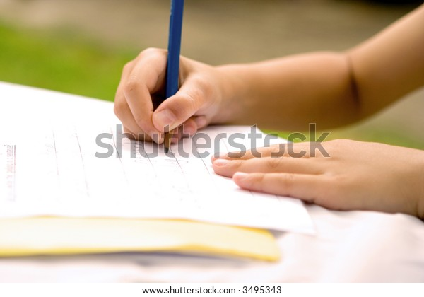 Young hands practising his writing skill, outdoors.