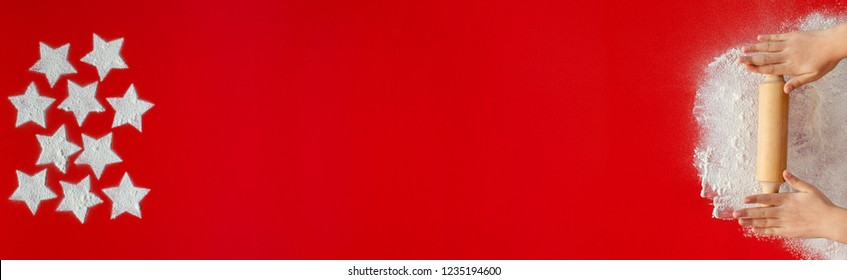 Young hands with rolling pin and christmas stars drawing in flour on red table - vivid scarlet background large copy space, horizontal or vertical xmas banner format