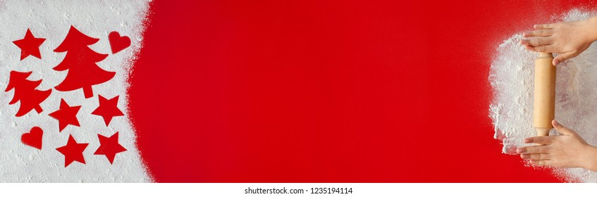 Young hands with rolling pin and holiday season shapes drawing in flour on red table - vivid scarlet background large copy space, horizontal banner format
