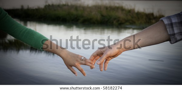 Young hands touching water in background.
