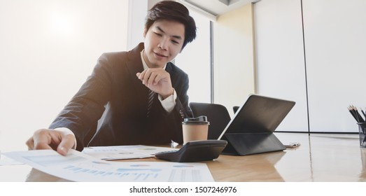 Young handsome accountant preparing financial reports for the next meeting in modern office