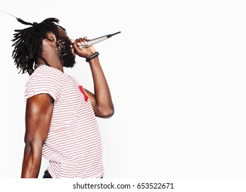 young handsome african american boy singing emotional with microphone isolated on white background, in motion gesturing smiling, lifestyle people concept