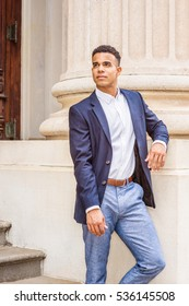 Young handsome African American Business Man in New York. Wearing blue blazer, white shirt, gray pants, a black college student standing by column outside on campus, looking up. Color filtered effect