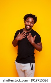young handsome african american guy student posing cheerful and gesturing on yellow background, lifestyle people concept