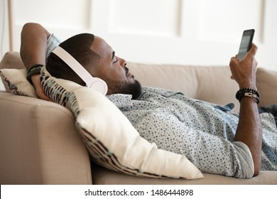 Young handsome african american happy man lying on pillow on comfy sofa, relaxing, listening favorite music in modern wireless bluetooth headphones, chatting in messenger, scrolling social networks.