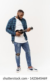 Young handsome african american man plays ukulele isolate over white background,