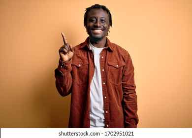 Young handsome african american man wearing casual jacket standing over yellow background showing and pointing up with finger number one while smiling confident and happy.