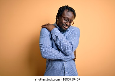 Young handsome african american man wearing shirt and glasses over yellow background Hugging oneself happy and positive, smiling confident. Self love and self care